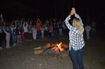 Campers and counselors singing by the fire.