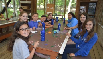 Smiling campers making jewelry
