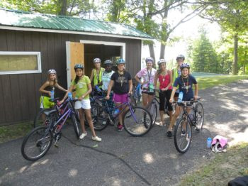 Campers getting ready to go on a bike ride.