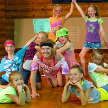 Campers and counselor showing off a dance routine