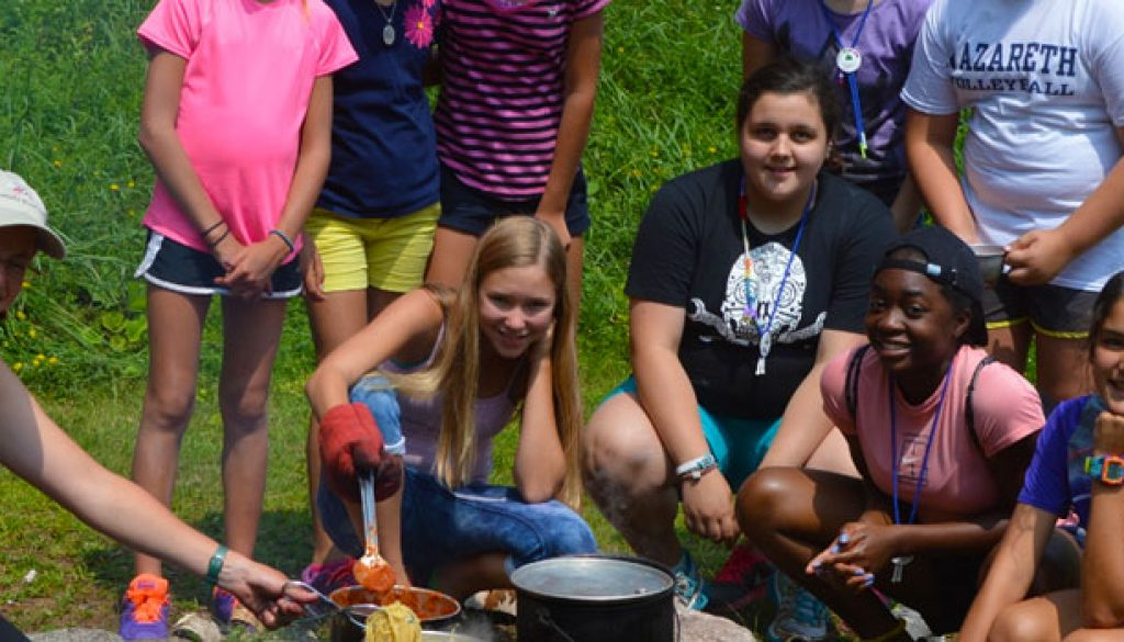 Learning how to cook over a fire at WeHaKee Camp for Girls