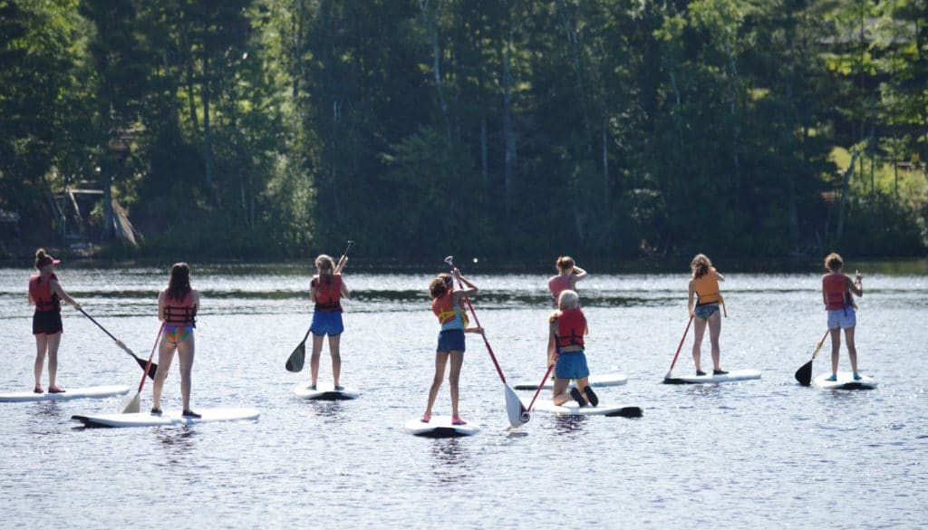WeHaKee Camp for Girls campers standing on paddle boards on Lake Hunter on a sunny day.