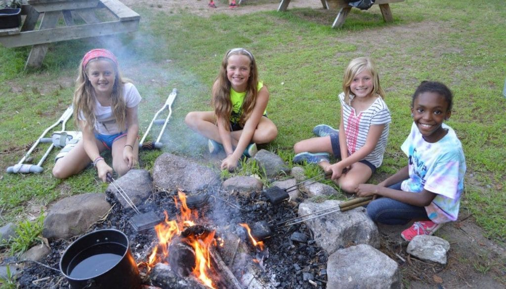 Campers making pudgy pies in the fire at WeHaKee Camp for Girls.