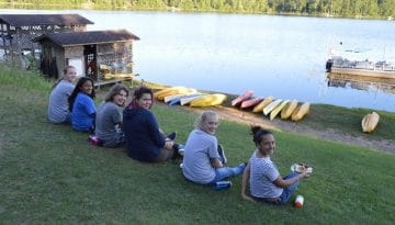 Campers enjoying lunch in front of Hunte Lake at WeHaKee Camp for Girls.