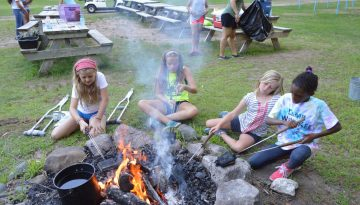 Campers making pudgy pies at the fire for supper at WeHaKee Camp for Girls.