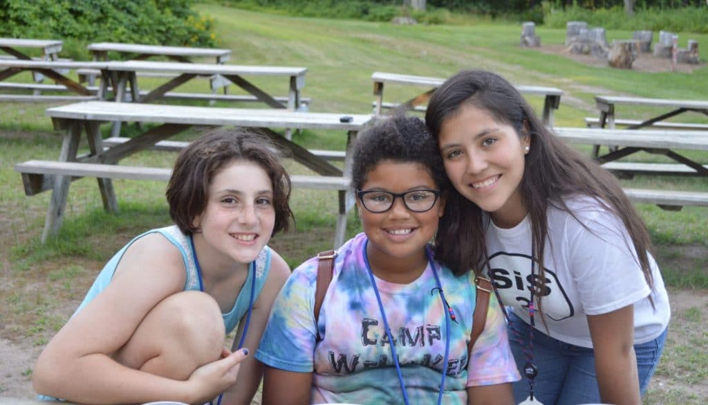 Camper friends hanging out around the picnic tables at WeHaKee Camp for Girls.