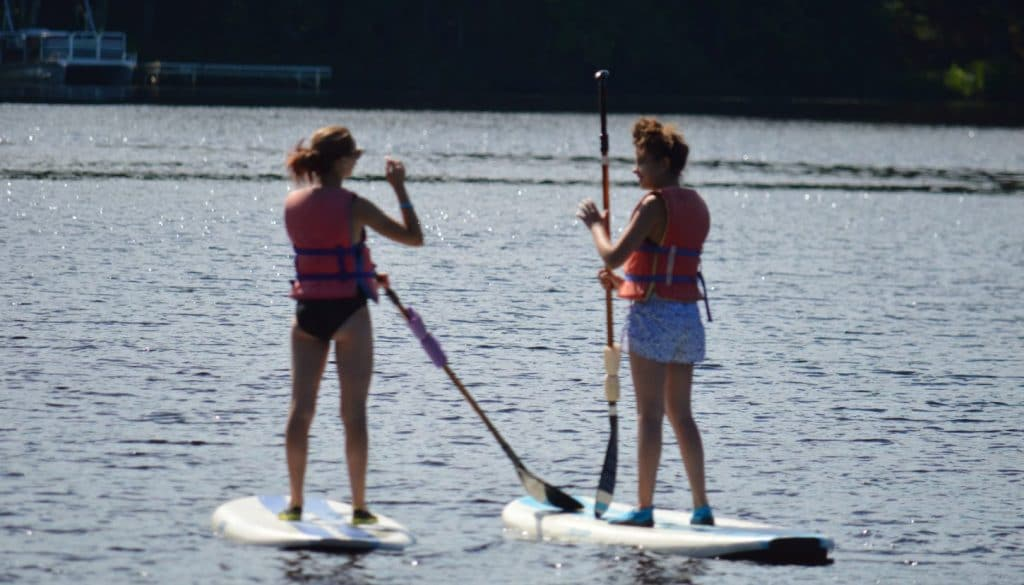 Camper friends standing on paddle boards on Hunter Lake at WeHaKee Camp for Girls.