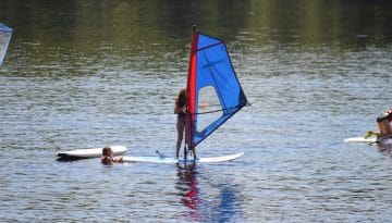 Campers paddle boarding with a sailor attached at WeHaKee Camp for Girls.