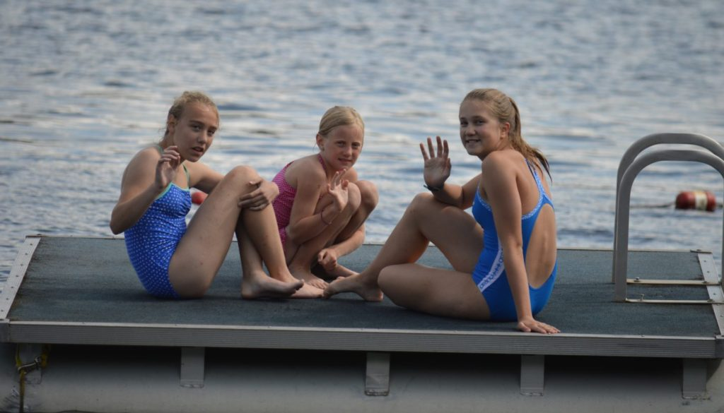Campers hanging out on the floating diving dock on Hunter Lake at WeHaKee Camp for Girls.