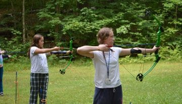 Campers practicing shooting bow and arrow and WeHaKee Camp for Girls.