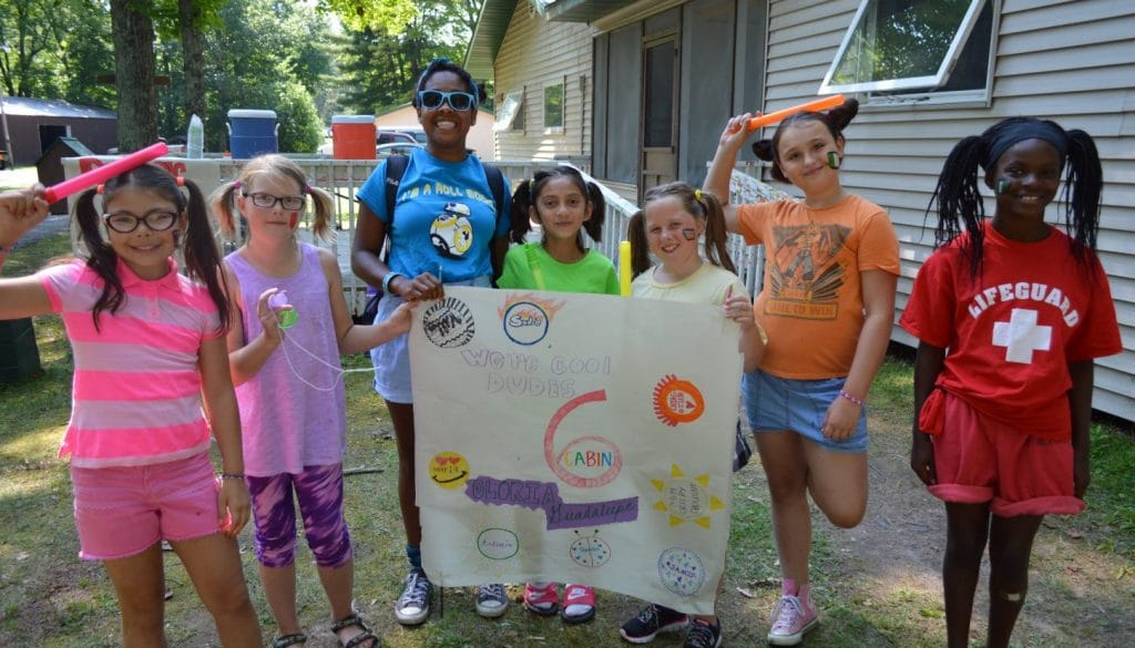 Campers from cabin 6 holding a sign they made at WeHaKee Camp for Girls.