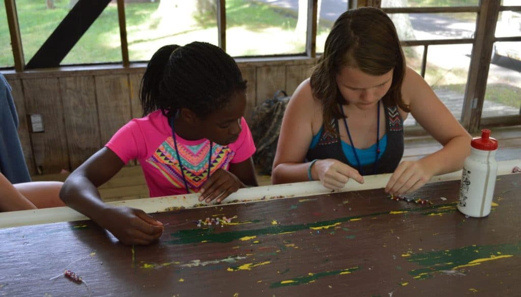 Two WeHaKee campers creating bracelets.