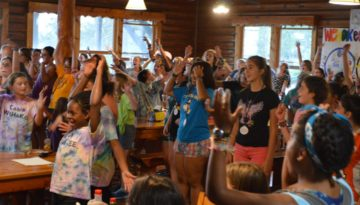 WeHaKee Camp for Girls campers singing and having fun indoors.