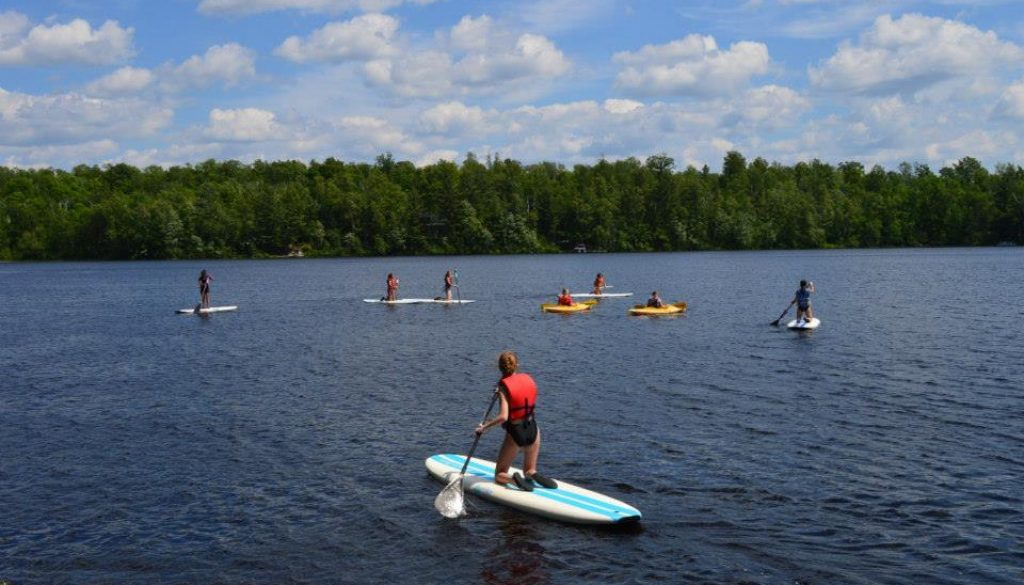 WeHaKee Camp for Girls campers paddleboarding and kayaking.