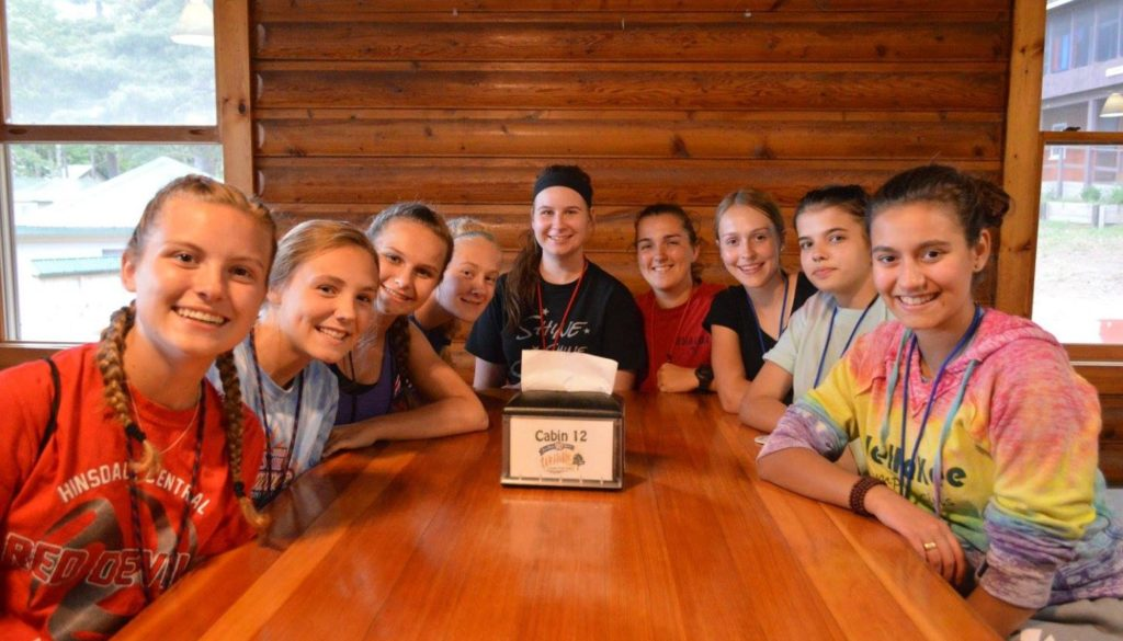 WeHaKee Camp for Girls staff members sitting around a camp table.