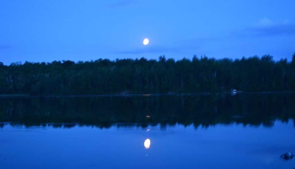 Moon above the trees across Hunter Lake.