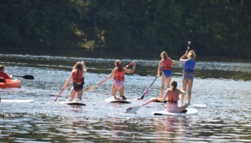 WeHaKee Camp for Girls Campers paddle boarding on Hunter Lake during water activities.