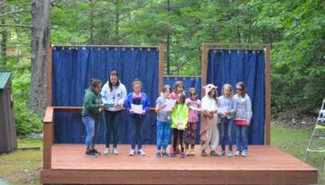 WeHaKee Camp for Girls campers and staff reading a skit on the outdoor stage.