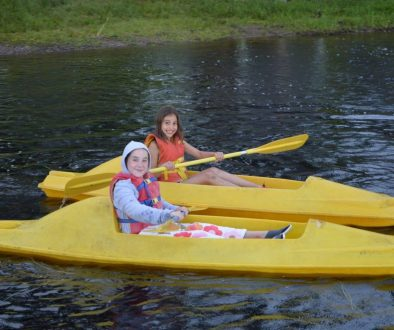 Two WeHaKee campers having fun on the lake in their yellow kayaks