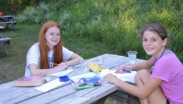 Two WeHaKee campers enjoying time together on a picnic table