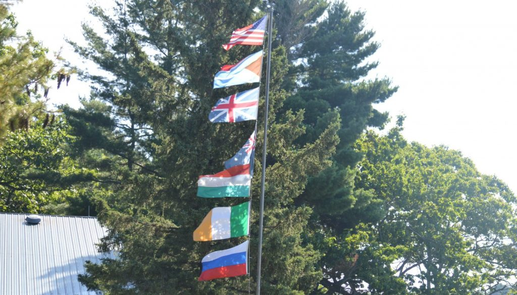 Country flags on a flag pole at WeHaKee Camp for Girls.