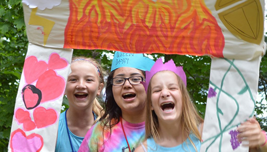 WeHaKee Camp for Girls Campers being silly with a cardboard frame.