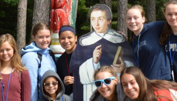WeHaKee Camp for Girls Campers posing around a cardboard person.