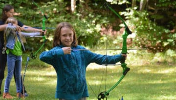 WeHaKee Camp for Girls happy camper with a bow and arrow.