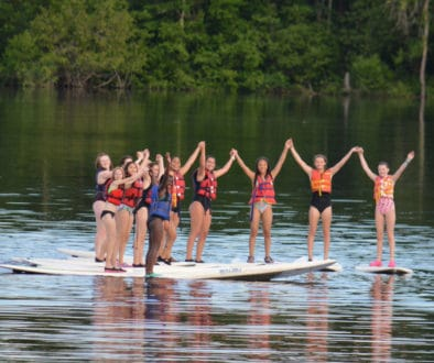 WeHakee Camp for Girls campers holding hands while standing on paddle boards.
