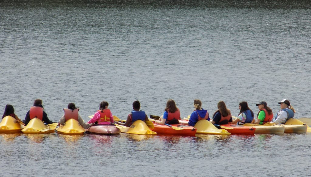 WeHakee Camp for Girls campers linking arms in kayaks.