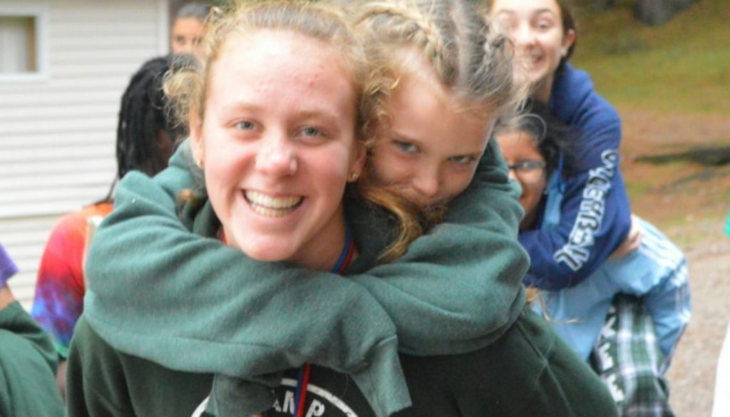 WeHakee Camp for Girls camper giving another camper a piggyback ride while walking amongst other campers.