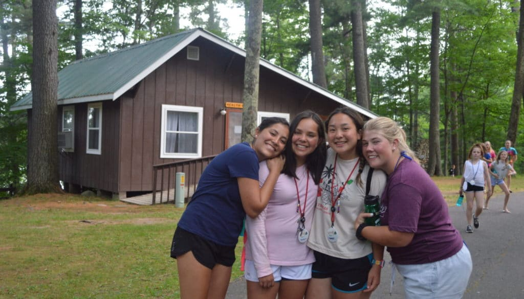 WeHakee Camp for Girls staff group photo in front of cabin.