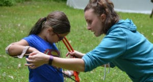 WeHaKee Camp For Girls employee assisting a camper with archery.