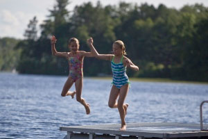 Girls jumping into the lake.